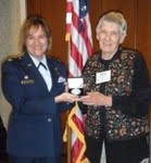 Colonel Roseanne Warner, US Air Force presents Dr. Naylor with medal.